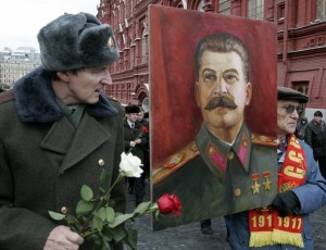 Russian communist supporters carry a portrait of Soviet dictator Stalin
